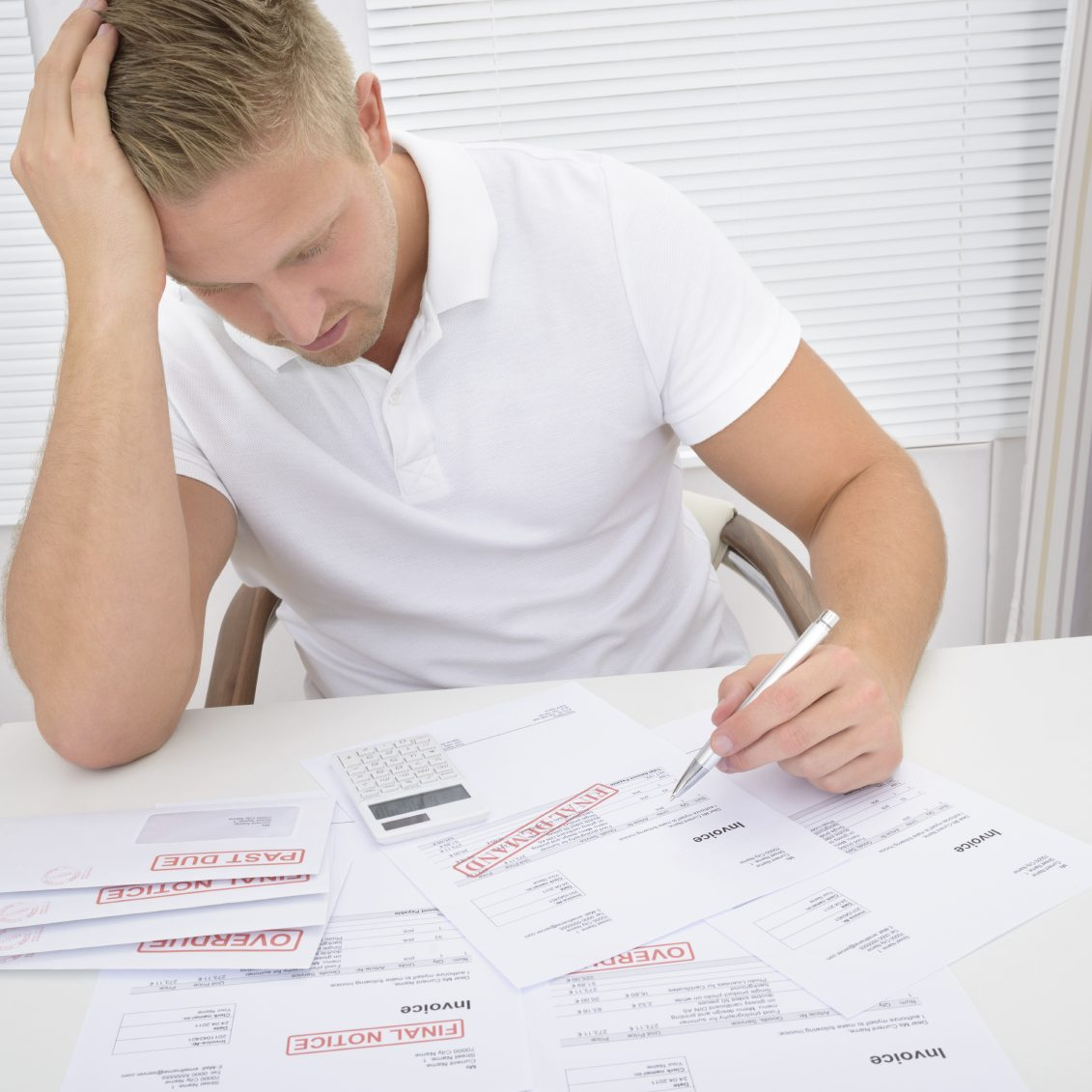 Portrait Of A Worried Man Calculating Unpaid Bills. Documents and stamps were created by photographer